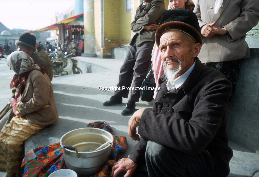 KASHGAR, 1 OCTOBER 2001:a group of beggars that belong tothe Kazakh minority sit ouside the mosque in Kashgar.Kazakhs belong to the poorest minorities in western china.UUighur muslims in China's western Xinjiang province mostly stick to islamic lifestyles due to their proximity to Afghanistan & Pakistan .Today, 47 percent of Xinjiang is Uighur and 41 percent is Han. Smaller groups of other Turkic Muslims, including Kyrgyz, Kazakhs, Tajiks and Uzbeks, make up the remainder of the population ..The government maintains tight control over Uighur culture.All mosques are required to register with the government. In 2001, authorities called in 8,000 imams for special training on the Communist Party's ethnic and religious policies. In 2002, Xinjiang's top university eliminated all instruction in the Uighur language. .. . .
