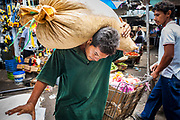 08 JANUARY 2007 - MANAGUA, NICARAGUA:  A man delivers beans to vendors in Mercado Oriental, the main market that serves Managua, Nicaragua. The market encompasses dozens of square blocks and is the largest market in Central America.  Photo by Jack Kurtz