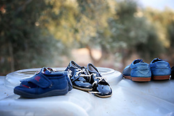 Children's shoes that have been cleaned are left to dry on top of a water tank in a settlement camp for Syrian refugees situated amongst an olive grove in Koura, near Tripoli, Lebanon.
