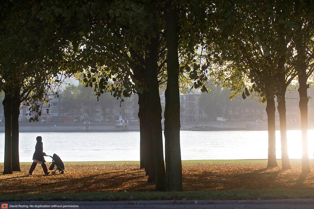 Nederland Rotterdam 18-09-2009 20090918 Foto: David Rozing    Moslima wandelt met buggy langs het water op een mooie zonninge herfstdag, Kralinger Esch. Ouderschap.                                                    .Foto: David Rozing