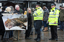 © Licensed to London News Pictures. 01/01/2017. Atherstone, North Warwickshire, UK. Atherstone Hunt meeting in the Market Square for their New Years Day meet. Pictured, Anti Hunt protestors take up a position in the centre of the Market Square but are monitored by the Police. Photo credit: Dave Warren/LNP