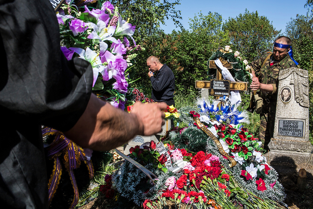 HORLIVKA, UKRAINE - MAY 24: Men lay flowers over the grave of Aleksandr Politov, a pro-Russia militia fighter who was killed when his group attacked a Ukrainian military checkpoint two days earlier in the village of Blahodatne, on May 24, 2014 in Horlivka, Ukraine. Presidential elections are scheduled for tomorrow, but pro-Russia militias have been seeking to prevent them from being administered throughout the eastern part of the country. (Photo by Brendan Hoffman/Getty Images) *** Local Caption ***