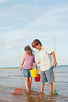 Brother and Sister in surf on beach with buckets and small fishnets
