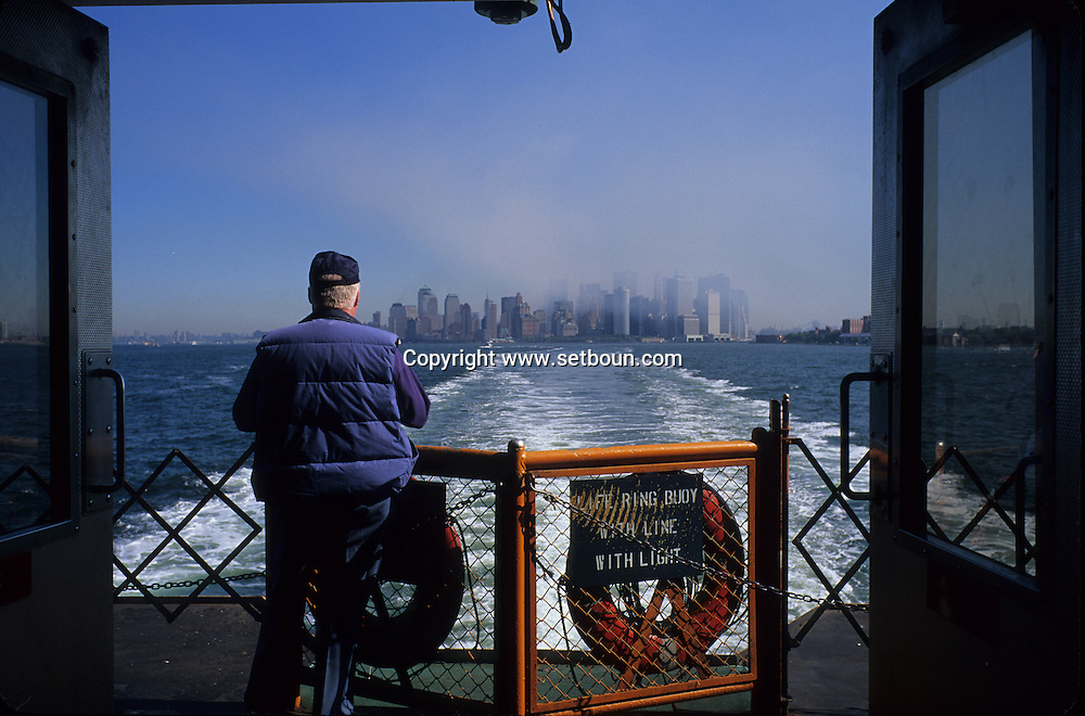 New York. old man watching The destroyed skyline view from Staten island  Ferry. after the terorist attack on world trade center towers in Manhattan  New york  Usa /   viel homme regardant Le skyline detruit vu depuis le staten island ferry . Apres l'attaque terroriste sur les tours du world trade center a Manhattan  New york  USA