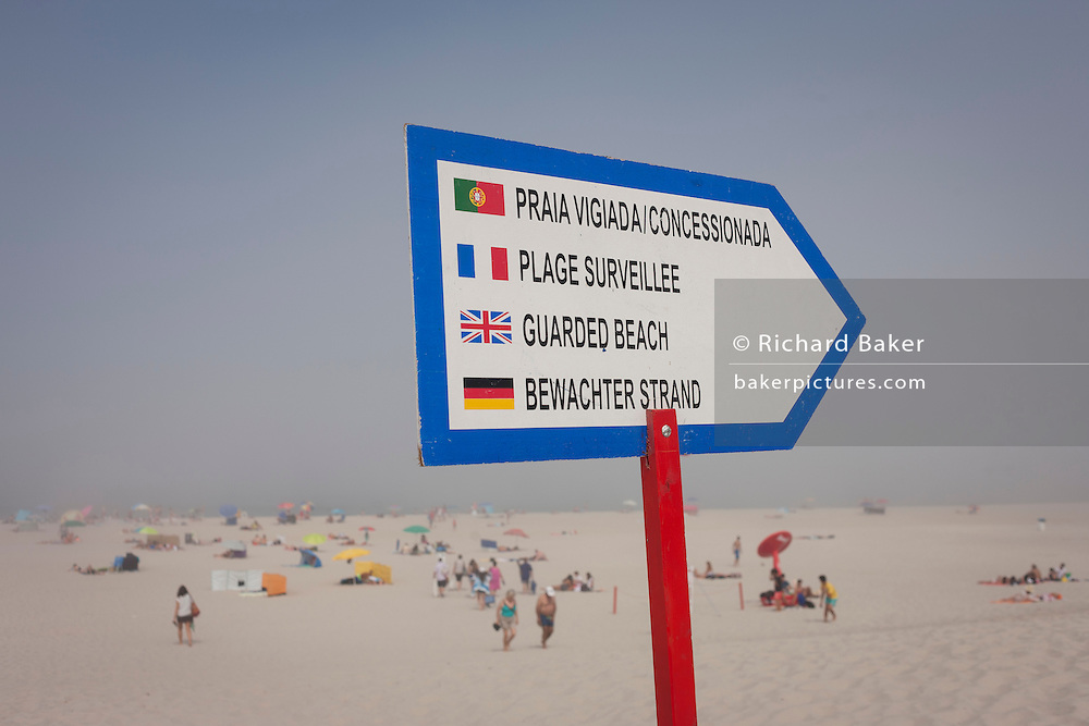 A warning sign in four languages telling sea swimmers of the dangers on this Portuguese beach that only one side is guarded by lifesavers, on 18th July 2016, Costa Nova, near Aveira, Portugal. The Portuguese, French, English and German writing should inform most of those thinking of entering the rough waters, especially with mist rolling in. (Photo by Richard Baker / In Pictures via Getty Images)