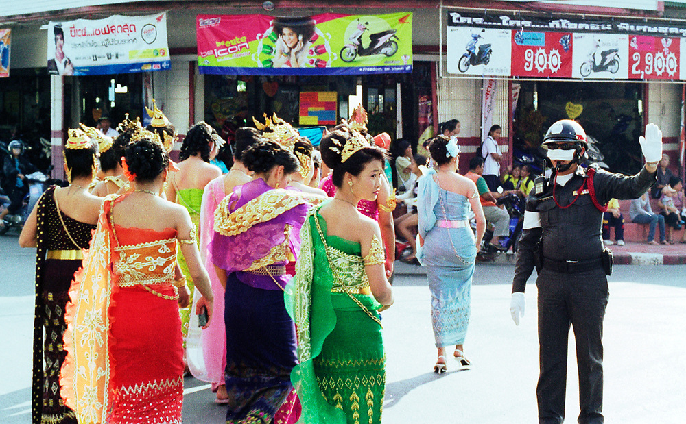 Lopburi, Thailand. During a local celebration, a group of women wearing traditional thai dress is crossing the street under the harsh sun of midday.<br />