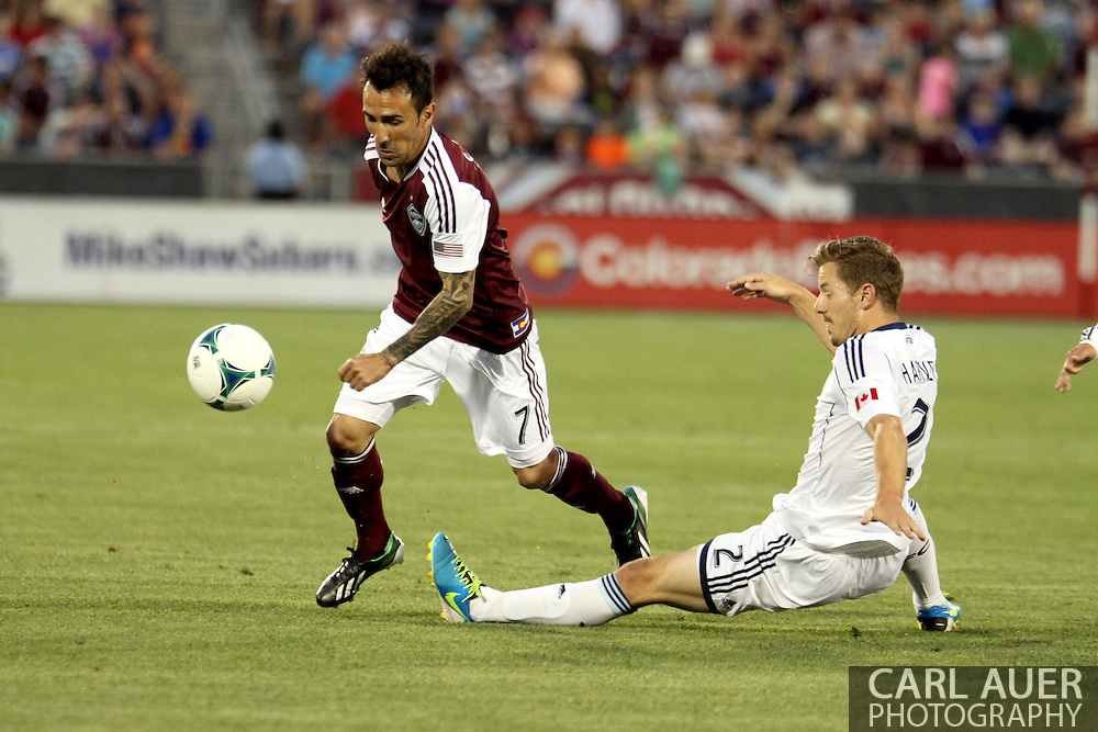 August 17th, 2013 - Colorado Rapids forward Vicente Sánchez (7) attempts to avoid the tackle from Vancouver Whitecaps FC defender Jordan Harvey (2) in the first half of the Major League Soccer match between the Vancouver Whitecaps FC and the Colorado Rapids at Dick's Sporting Goods Park in Commerce City, CO