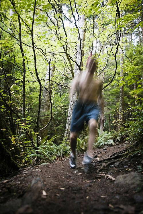 A man trail running on the Little Si Trail near North Bend, Washington, USA.  Blurred.