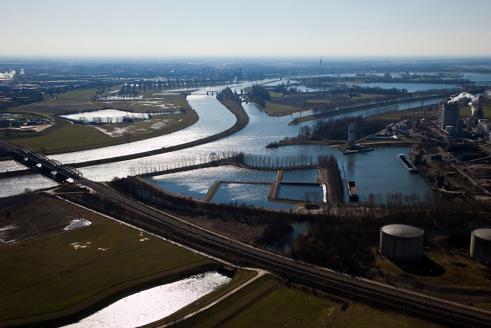 Nederland, Limburg, Gemeente Leudal, 07-03-2010; rivier de Maas in de omgeving van Buggenum, gezien naar Roermond. Links de spoorbrug, midden links de rivier met stuw, rechts het Lateraalkanaal Linne-Buggenum. Geheel rechts de Willem-Alexander Centrale van Nuon, stoom- en gascentrale die werkt op kolenvergassing (ook vergassing biomassa). Vroegere lokatie  Maascentrale.   .River Meuse near Buggenum. Left the railway bridge, center left the river weir, and Roeromnd at the horizon, to the right Lateral channel Buggenum-Linne. Far right the Willem-Alexander Centrale (Nuon), steam-cycle plant operating on coal gasification (including biomass gasification)..luchtfoto (toeslag), aerial photo (additional fee required);.foto/photo Siebe Swart