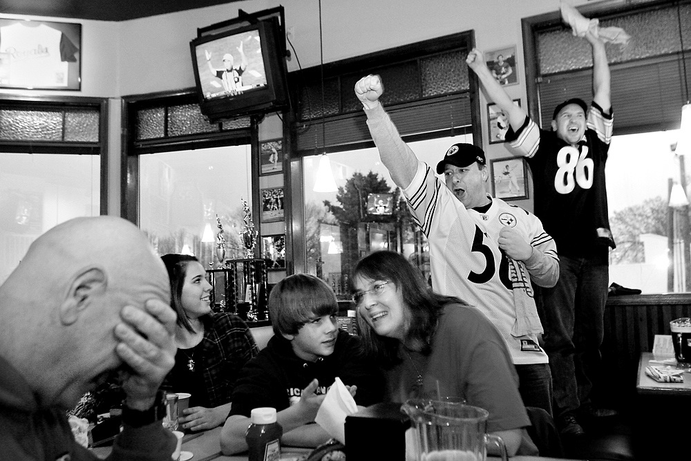 Steelers fans Tim Hager, right, of Yakima, and Alan Masterman of Richland celebrate Rodney Harrison's 100-yard touchdown off an interceptiton at the end of the first half as the Mann family of Richland watches in disbelief as football fans gathered at Jackson's in Richland to watch Super Bowl XLII. The Steelers defeated the Cardinals 27-23.