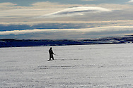 Sasa Samson, age 37, the best Inuit hunter in the Inuit town of Resolute Bay, Canada, stands next to the breathing hole of a seal on Tuesday, June 12, 2007.  Sasa hunts seals for food, and his community uses every part of the seals, either eating the meat or using the hides to make warm clothes. Sasa often stands next to the breathing hole of the seal without moving for 30 minutes or more to capture the animal with with his hooked stick when it rises to the surface to breathe.   .. The traditional way of life in the Resolute Bay Inuit community is being threatened by rising temperatures.  The dangers of global warming, which have been extensively documented by scientists, are appearing first, with rapid, drastic effects, in the Arctic regions where Inuit people make their home.  Inuit communities, such as those living on Resolute Bay, have witnessed a wide variety of changes in their environment.  The ice is melting sooner, depleting the seal population and leaving them unable to hunt the animals for as long.  Other changes include seeing species of birds and insects (such as cockroaches and mosquitoes) which they have never encountered before.  The Inuit actually lack words in their local languages to describe the creatures they have begun to see.