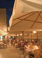 People eating at an outdoor restaurant in<br /> the evening, Dubrovnik, Croatia<br /> c. Ellen Rooney