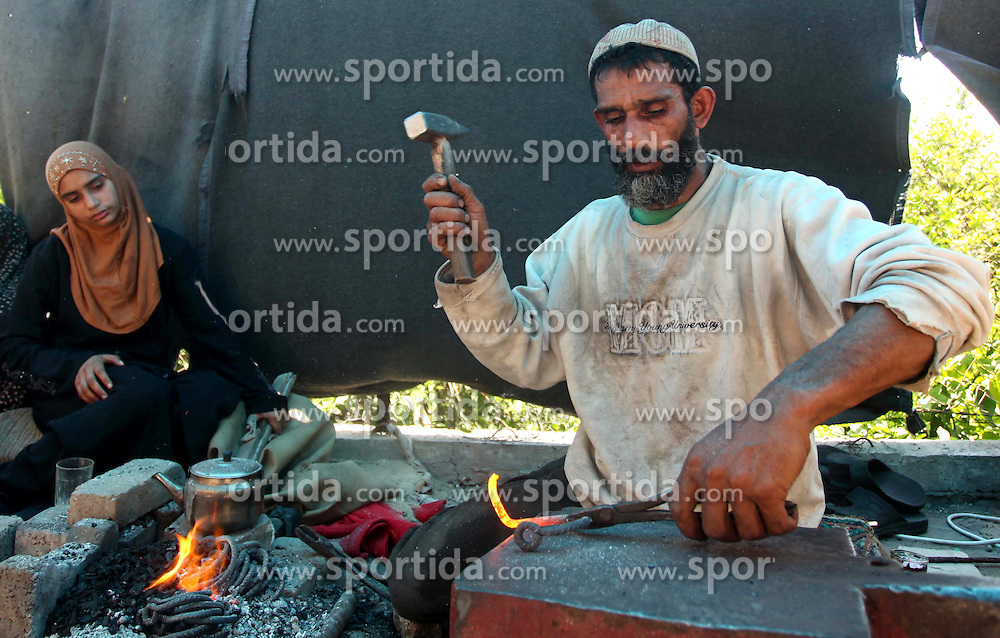30.04.2015, Gaza Stadt, PSE, Schmied Workshop, im Bild der Pal&auml;stinensische Schmied Ibrahim Mustafa arbeitet bei seiner kleinen Werkstatt // Palestinian blacksmith Ibraheem Mustafa, 40-year-old, hammers heated steel, at his small workshop in Gaza city. The ILO estimates that the 2014 conflict in Gaza raised unemployment from 32.6 per cent to 36.9 per cent, which caused an estimated daily loss in economic activity of US$ 508,000 per working day since August 2014. As the numbers of the unemployed laborers in Gaza reached 200,000 and poverty to 60 per cent, according to local reports, Palestine on 2015/04/30. EXPA Pictures &copy; 2015, PhotoCredit: EXPA/ APAimages/ Ashraf Amra<br /> <br /> *****ATTENTION - for AUT, GER, SUI, ITA, POL, CRO, SRB only*****