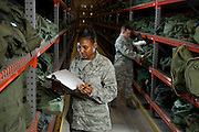 A U.S. Air Force Staff Sgt. takes inventory of the military issued gear on the deployment line...All Airman who are preparing to deploy must go through the mobility line. There are Airman in charge of keeping supply levels up, inventorying and issuing the gear. Certain military kits are contained in olive drab colored duffle bags and grouped by contents.