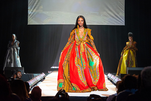 A model in a colorful dashiki-print dress walks down the runway at the Howard University Annual Fashion Show.