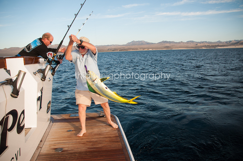 Father and son bring a Durado fish on board his boat, Ocean Pearl, in the Sea of Cortez. Deep Sea fishing is a huge industry in Mexico.