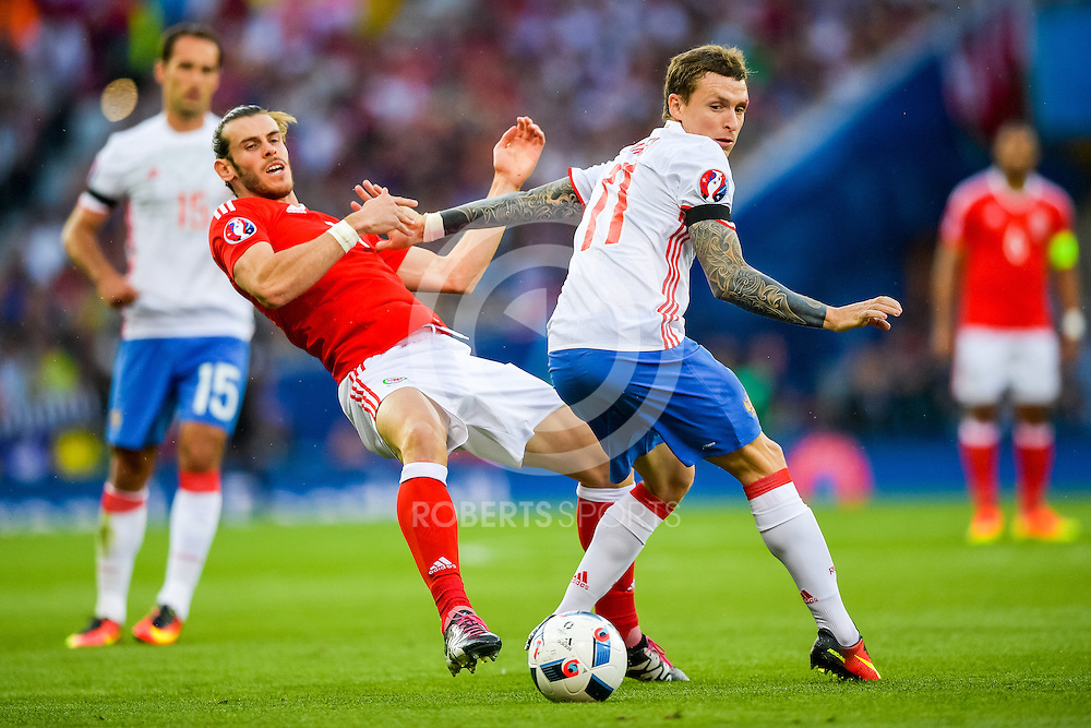 Wales' Gareth Bale gets a push from Russia's Pavel Mamaev. Action from the WALES v RUSSIA game at UEFA EURO 2016 in Toulouse, 20 June 2016. (c) Paul J Roberts / Sportpix.org.uk