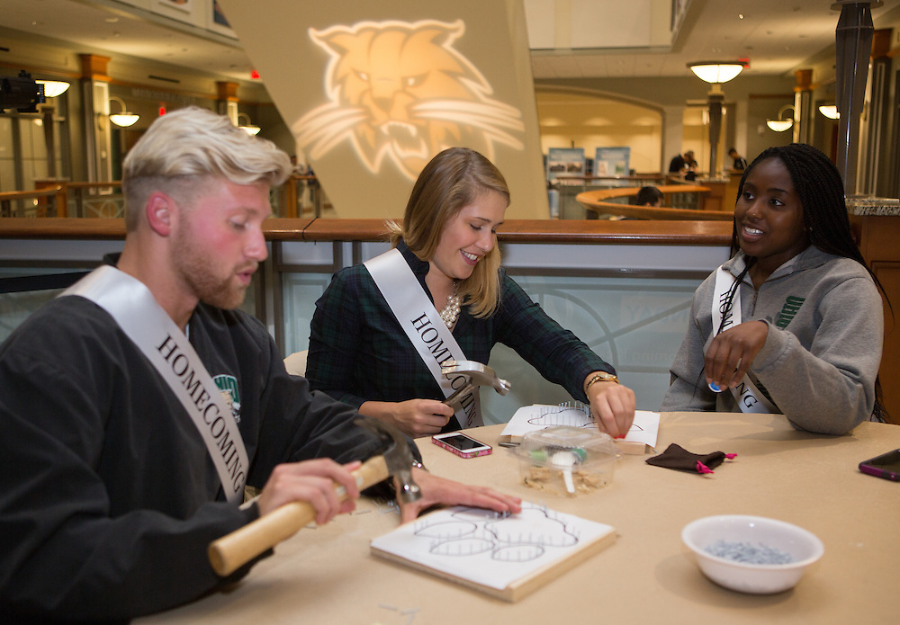 From left: Ben Clos and Kaija Nealon create Ohio University-themed string art pieces during a Homecoming how-to event hosted by the Campus Involvement Center in Baker Center Theater Lounge on Oct. 7, 2014. Zainab Kandeh mlooks on. Photo by Lauren Pond