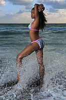 Sensual african american getting a bath in the ocean early morning.
