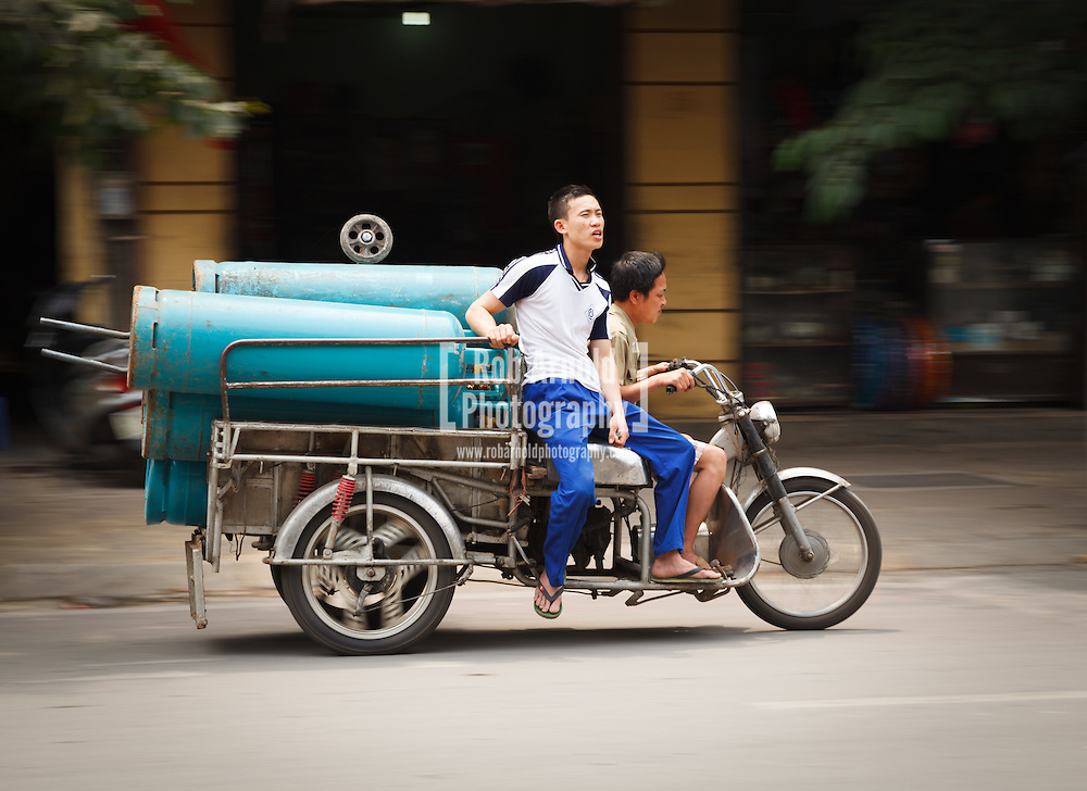 © Rob Arnold.  19/04/2013. Hanoi, Vietnam. Two men on a motorcycle precariously carrying large gas cylinders through the streets of Hanoi. Photo credit : Rob Arnold
