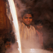on a winter night in old delhi, hot milk is mixed to be used for masala chai at a chai stall.