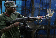 A Liberian government gunman fires whilst waving a curse at the enemy at accross the  'Old Bridge' in torrential rains, Monrovia 28 July 2003. LURD(Liberians United for Reconciliation and Democracy) rebels drove government forces back over the bridge last night leaving the government forces on the Monrovia side of the bridge defending the city.This the Tenth day of continued fighting for the capital despite the call for ceasefire and heavy rains.<br /> EPA PHOTO/NIC BOTHMA