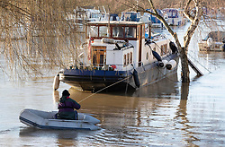 © Licensed to London News Pictures. 23/12/2019. Wateringbury, UK. A man in a dinghy pulls himself on a rope towards his houseboat to attempt to move it off a tree (R) in Wateringbury, Kent. River levels are slowly beginning to drop after days of heavy rain in the south. Photo credit: Peter Macdiarmid/LNP