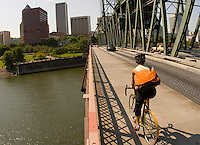 A young woman bike commuting across the Hawthorne Bridge in Portland, Oregon.