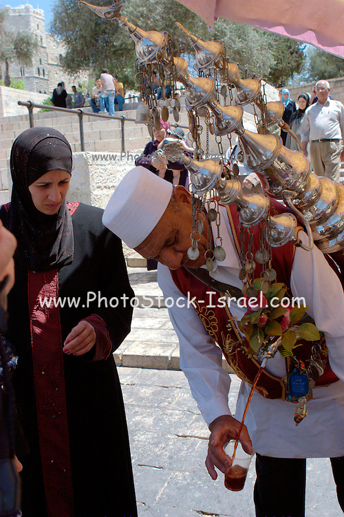 Israel, Jerusalem, Old City Man in traditional clothes selling tamarind juice in front of Damascus gate