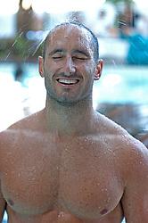 Shirtless Caucsian man enjoying a shower