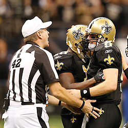 December 26, 2011; New Orleans, LA, USA; New Orleans Saints quarterback Drew Brees (9) receives the ball from referee Jeff Triplette (42) as he celebrates after breaking the NFL single-season passing record formerly held by Miami Dolphins quarterback Dan Marino on a 9-yard touchdown throw to Darren Sproles during the fourth quarter of a game against the Atlanta Falcons at the Mercedes-Benz Superdome. The Saints defeated the Falcons 45-16. Mandatory Credit: Derick E. Hingle-US PRESSWIRE