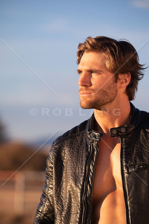 hot guy in a leather jacket outdoors at sunset