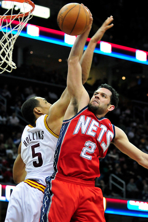 March 23, 2010; Cleveland, OH, USA; New Jersey Nets point guard Jordan Farmar (2) drives in for a dunk over Cleveland Cavaliers center Ryan Hollins (5) during the third quarter at Quicken Loans Arena. The Nets beat the Cavaliers 98-94 in overtime. Mandatory Credit: Jason Miller-US PRESSWIRE