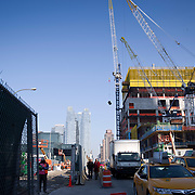 A couple walk along 35 Hudson Yards, AKA Equinox Tower, as a crane hoists equipment to the job site.  Designd by Skidmore, Owings & Merrill LLP and developed by Related Companies the skyscraper office tower will be 1,0009 feet tal upon completion.