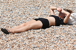 © Licensed to London News Pictures. 16/07/2014. Brighton, UK. A woman shading her eyes from the sun while  sunbathing on Brighton beach at lunchtime. Temperatures in parts of the south east are expected to hit 30 degrees this week. Photo credit : Hugo Michiels/LNP