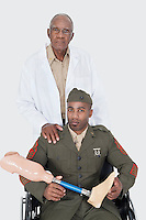 Portrait of senior doctor with US military officer holding artificial limb as he sits in wheelchair over gray background