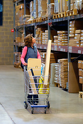 Woman warehouse shopping in IKEA Croydon South London UK