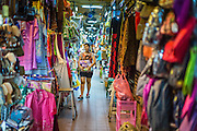 29 JULY 2014 - HAT YAI, SONGKHLA, THAILAND:  A woman walks through the market in Hat Yai. Hat Yai is the 4th largest city in Thailand and the largest outside of the Bangkok metropolitan area. It's less the 50 miles from the Malaysian border and is a popular vacation spot for Malaysian and Singaporean tourists.       PHOTO BY JACK KURTZ