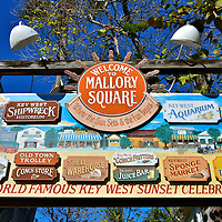 """Mallory Square Signage in Key West, Florida<br /> Above the list of stores and attractions on this sign for Mallory Square is the slogan: """"Where the Sun Sets and the Fun Begins."""" By day, tourists shop in this Old Town square.  As dusk approaches, people line up along the waterfront to watch the sun set over the Atlantic. The daily event is aptly called the """"Sunset Celebration.""""  This party tradition, which began in the late 1960s, is surrounded by musicians, street entertainers and of course food and drink.  The square is named after Stephen Russell Mallory. He was the son of Ellen, the first white woman to settle in Key West in 1823.  He became a U.S. Senator and Secretary for the Confederate Navy."""