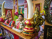 """28 FEBRUARY 2013 - BANGKOK, THAILAND: The manager of the Chuchok shrine in Bangkok waits for people to come and pray. The Chuchok Shrine is in suburban Bangkok. More than 100 people a week come to the shrine to pray for good fortune or good health. People whose prayers are answered return to the shrine with """"coyote dancers"""" to make merit and thank Chuchok. Coyote dancing is a Thai phenomenon created after the US movie """"Coyote Ugly"""" where attractive young women dance in a sexually suggestive way, usually for pay. They're common at bars and festivals. Coyote dancers are typically better paid than other Thai women in the hospitality industry and usually are not allowed to date or see customers are off the dance floor. Coyote dancers perform at the Chuchok shrine because according to Buddhist literature Chuchok was a relatively repulsive old hermit and Brahmin priest who was cared for by a young woman after he made her family's wishes come true.   PHOTO BY JACK KURTZ"""