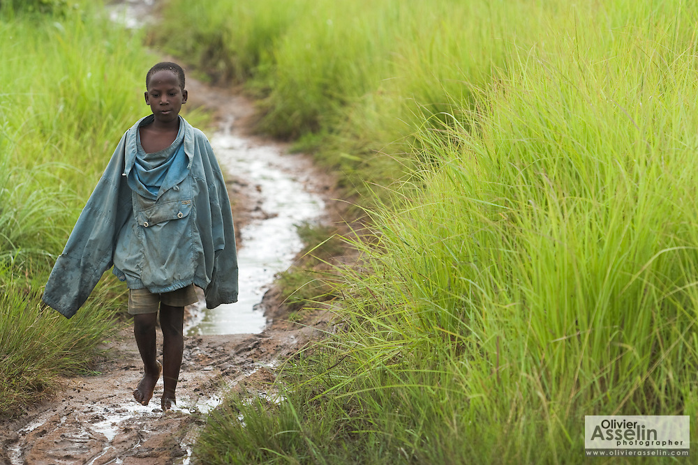 A boy walks on a muddy footpath leading to the village of Lalo, Benin on Tuesday September 18, 2007.