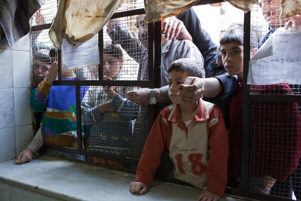 Hungry hands reach through the window of the bread factory, with money to buy the day's bread, early morning, Aleppo
