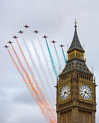 © Licensed to London News Pictures. 12/11/2015. London, UK. The Royal Air Force aerobatic team The Red Arrows, trailing the orange and green colours of the Indian flag during a fly past Big Ben and the The Houses of Parliament as part of a three day visit of India's Prime Minister Narendra Modi to the UK.  Photo credit: Ben Cawthra/LNP