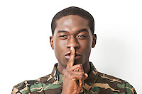 Portrait of young military soldier in camouflage clothing making silent gesture against white background