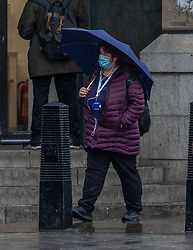 © Licensed to London News Pictures. 28/04/2020. London, UK. A women holds an umbrella in Westminster as Members of the public go to work during lockdown as heavy rain hits London after the warm sunny weather over the weekend. Today temperatures are expected to only reach 10c. London has also seen an increase in traffic and busier High Streets as more shops and cafes start to open up during the coronavirus pandemic crisis. Photo credit: Alex Lentati/LNP