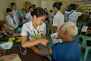 A Filipina nursing student takes a man's blood pressure at a clinic in Manila, the Philippines.