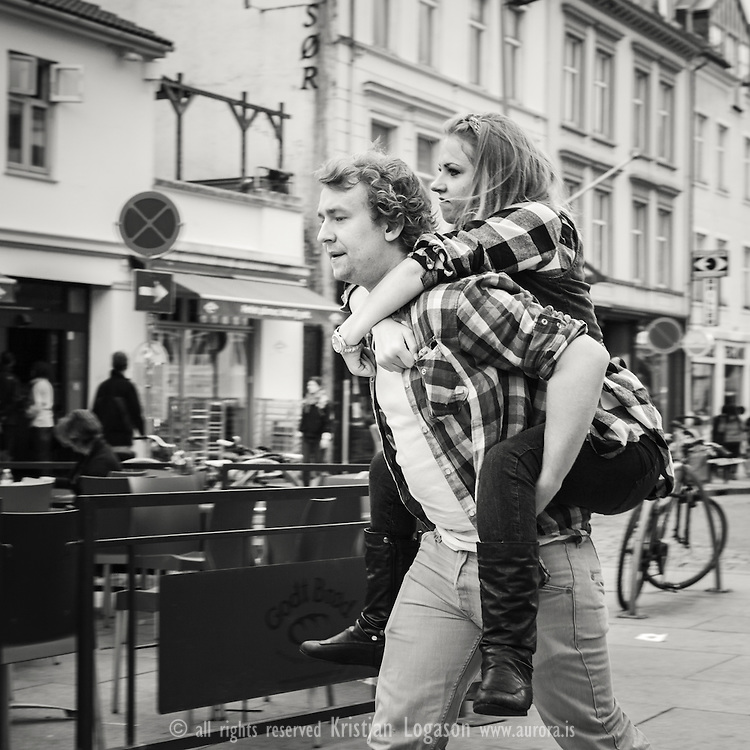 Man carrying a woman on his back in the streets of Bergen Norway