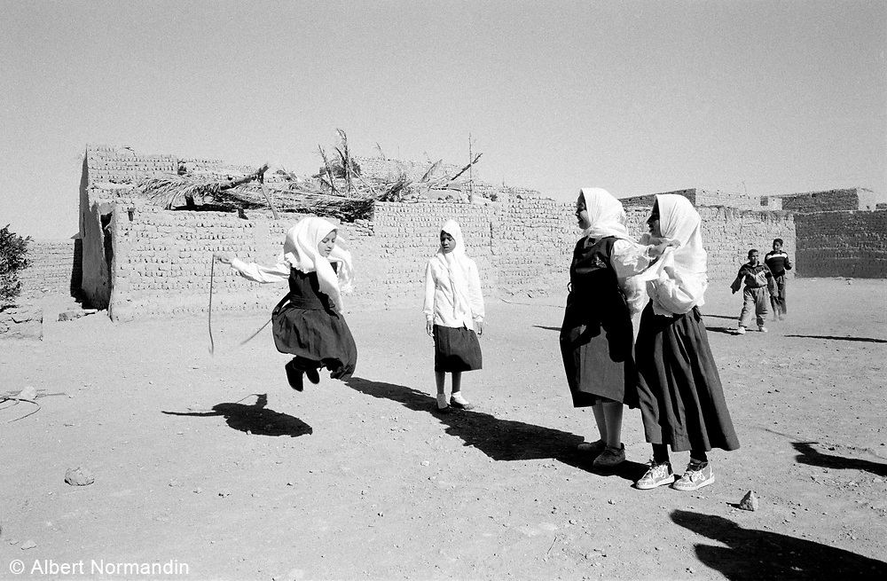 School girls in full traditional clothing skipping rope in schoolyard
