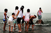 A group of Chinese tourist enjoy a day out in the beach at the popular city of Qingdao in Eastern China.