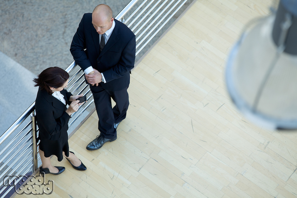 Business executives standing together while businesswoman using mobile phone